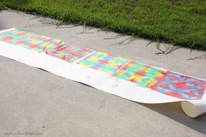 Opened up colored paper towels laid on clean paper on the side walk to dry in the sun,