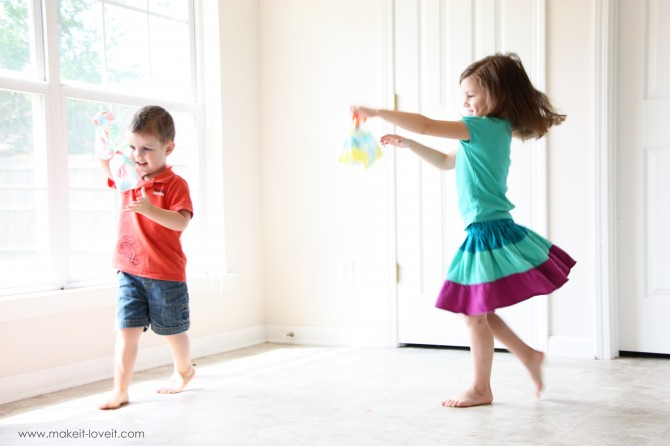Two children playing with butterflies making them fly around a room.