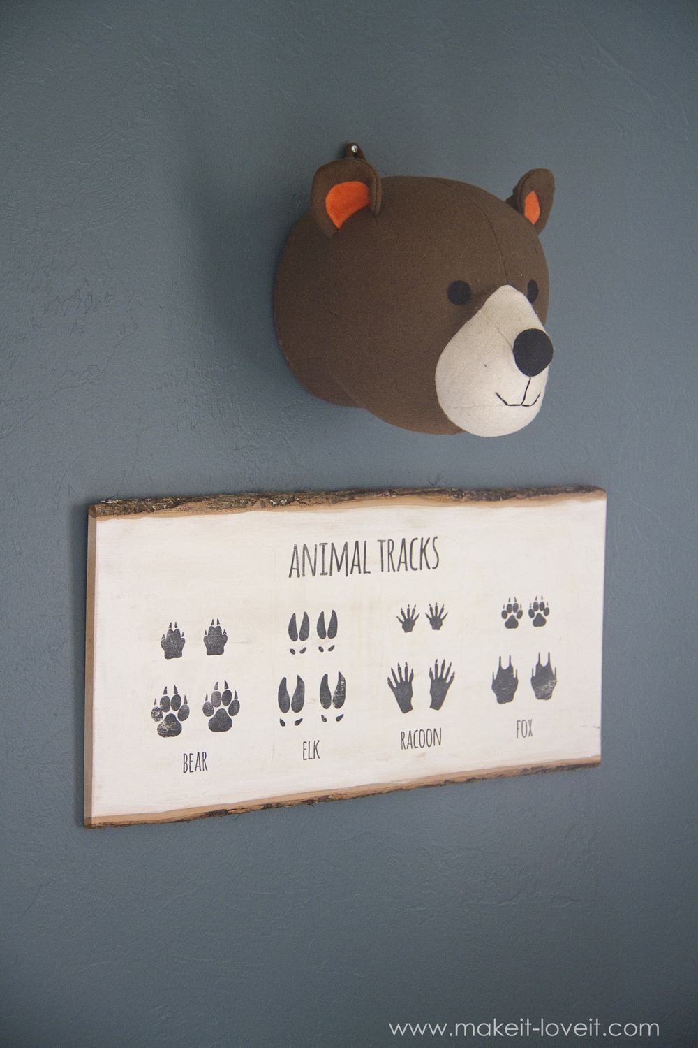 Cute  I did another image transfer of little baby and full grown animal tracks on this slab of wood Hangs perfectly beneath that stuffed bear head right
